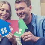 Couple with 3 house symbols – choice concept. They are sitting down, smiling, both casually dressed and holding green, blue and red house symbols which could represent also environmental conservation or home ownership, or property development.