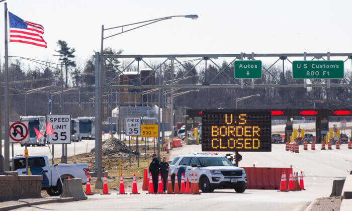 TOPSHOT - US Customs officers stand beside a sign saying that the US border is closed at the US/Canada border in Lansdowne, Ontario, on March 22, 2020. - The United States agreed with Mexico and Canada to restrict non-essential travel because of the coronavirus, COVID-19, outbreak and is planning to repatriate undocumented immigrants arriving from those countries. (Photo by Lars Hagberg / AFP) (Photo by LARS HAGBERG/AFP via Getty Images)