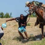A United States Border Patrol agent on horseback tries to stop a Haitian migrant from entering an encampment on the banks of the Rio Grande near the Acuna Del Rio International Bridge in Del Rio, Texas on September 19, 2021. - The United States said Saturday it would ramp up deportation flights for thousands of migrants who flooded into the Texas border city of Del Rio, as authorities scramble to alleviate a burgeoning crisis for President Joe Biden's administration. (Photo by PAUL RATJE / AFP)
